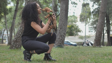 Girl kissing her little dog in a park