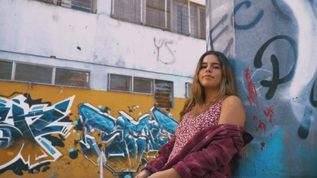 Girl leaning against a wall covered in graffiti