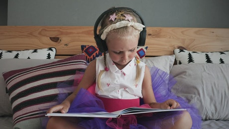 Girl listening to music and reading on the bed