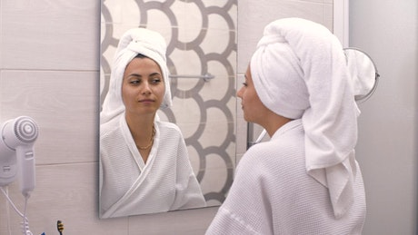 Girl looking and touching her face in a mirror