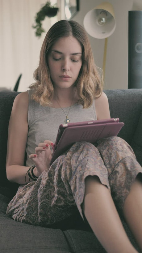 Girl lying in an armchair using an iPad