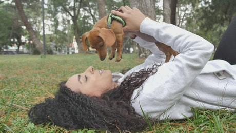 Girl lying on the grass holding her little dog on top