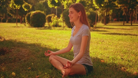 Girl meditating in yoga pose in a park