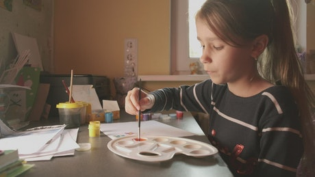 Girl mixing paints and painting