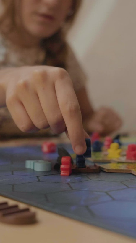 Girl moving small figures from a board game