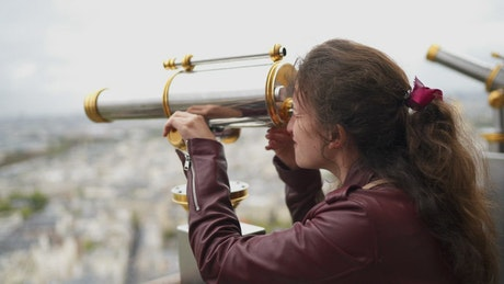 Girl observing Paris from the top of the Eiffel Tower