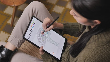 Girl on a sofa coloring flowers on a tablet