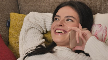 Girl on a sofa laughing during a phone call