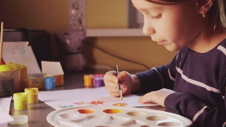 Girl painting with watercolors at home
