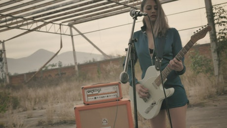 Girl playing guitar in a wasteland