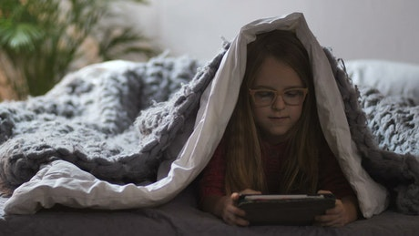 Girl playing with a tablet under a blanket