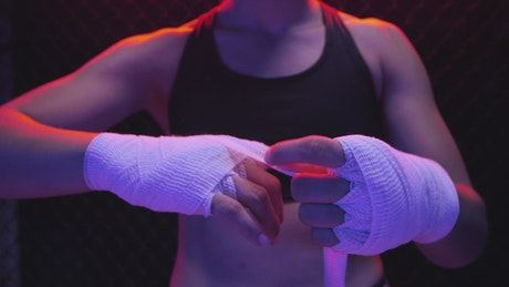 Girl putting a bandage on her hands before a fight
