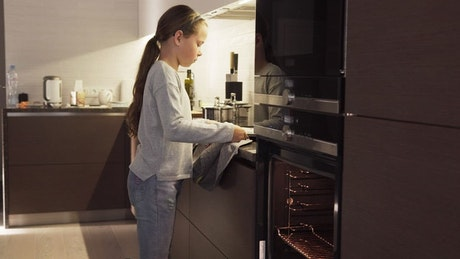 Girl putting cookies in an oven
