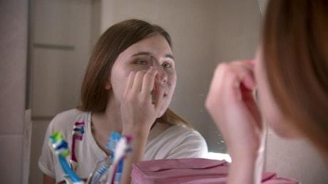 Girl putting on makeup in her bathroom mirror