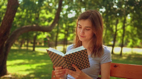 Girl reading a book in nature