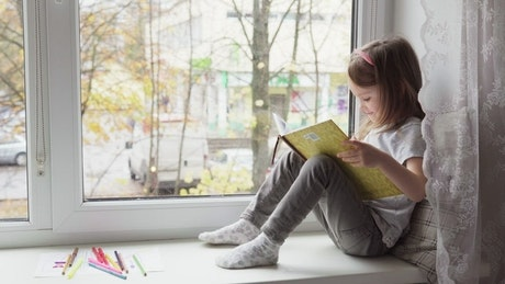 Girl reading by the window