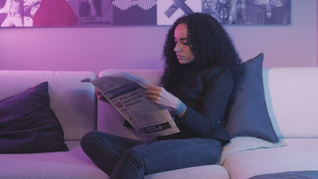 Girl reading the pages of a newspaper