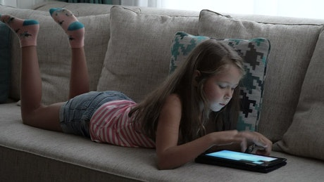 Girl relaxing with a tablet game