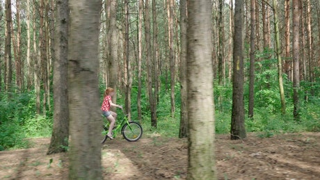 Girl riding a bicycle through a forest