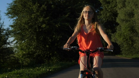 Girl riding a bike on a path in nature