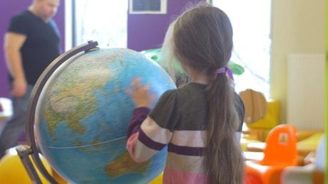 Girl rotating an earth globe at school