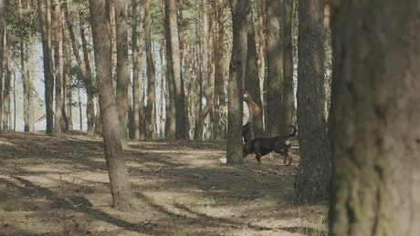 Girl running with her dog among the trees