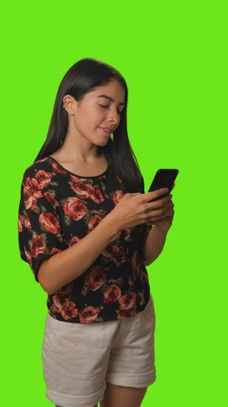 Girl sending a selfie by cell phone on a green background