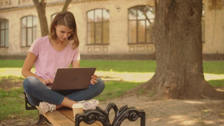 Girl sitting in a garden typing on a laptop