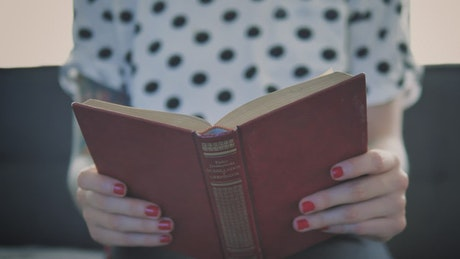Girl sitting in an armchair while reading a red book seen up close