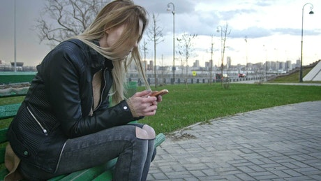 Girl sitting on a bench watching her cell phone