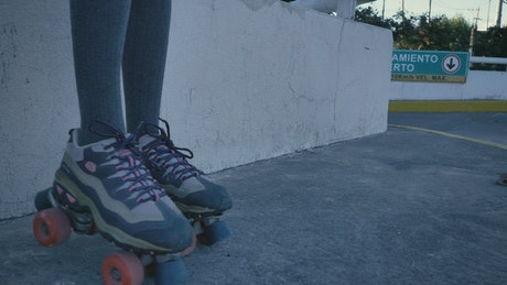 Girl sitting on a fence spinning the wheels of her skates