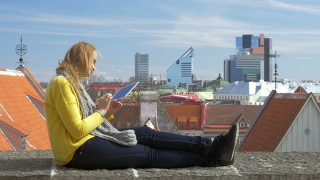 Girl sitting on a rooftop with her tablet