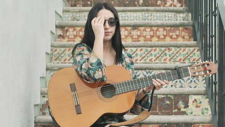 Girl sitting on a stairs starts to play her guitar
