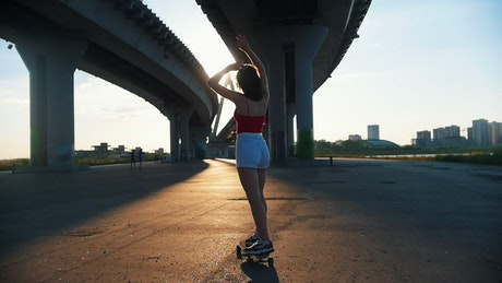 Girl skating in the afternoon under a bridge