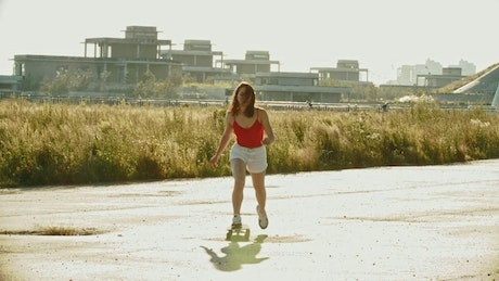 Girl skating outside on a sunny afternoon