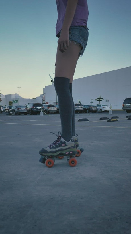 Girl skating slowly in a parking lot