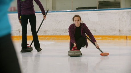Girl sliding on ice playing curling