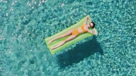 Girl sunbathing in the swimming pool