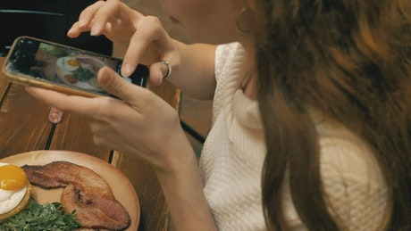 Girl taking a picture of her food in a restaurant