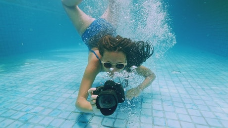 Girl taking underwater photos in a swimming pool