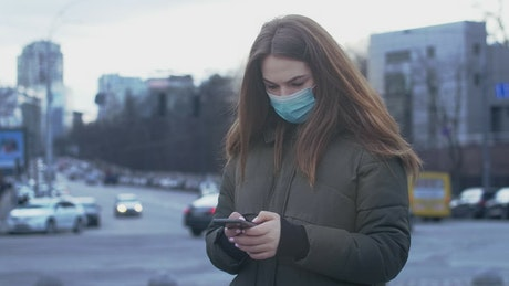 Girl texting with face mask on the street