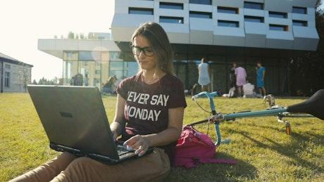 Girl types on laptop outside university building