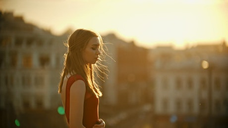 Girl under sunlight on top of a building