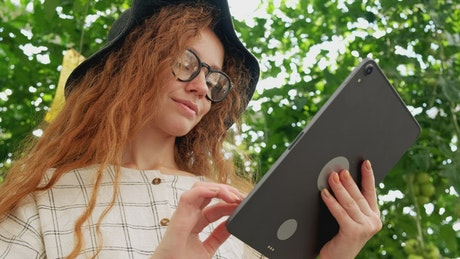 Girl using a big tablet in a garden