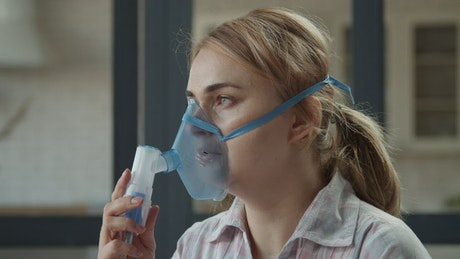 Girl using a nebulizer with mask