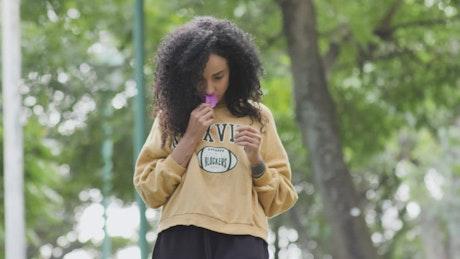 Girl walking in a park smelling a bougainvillea