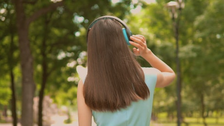 Girl walking in nature with music on her headphones
