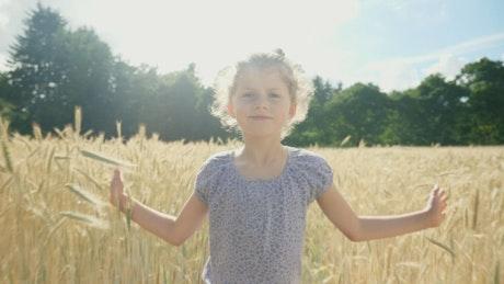 Girl walking through a wheat field