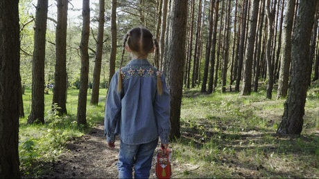 Girl walking through woodland with her bag
