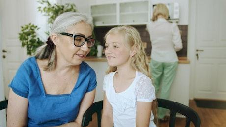 Girl whispers to grandma while mom cooks